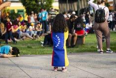 Bandera venezolana envuelta alrededor de niña joven en la protesta imagen de archivo