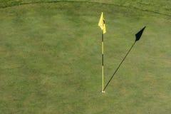 Bandera y agujero en el golf verde imagenes de archivo