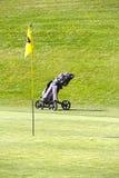 Bandera y carretilla el campo del golf Foto de archivo