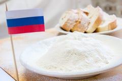 Bandera y harina rusas en una placa Rebanadas de pan en el fondo defocused Foto de archivo