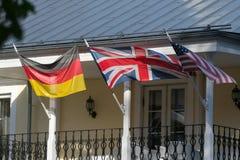 Banderas alemanas, británicas y americanas que agitan en el viento en la casa vieja fotografía de archivo