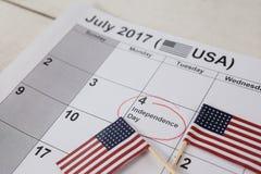 Banderas americanas con el cuarto del calendario de julio Fotografía de archivo