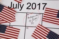 Banderas americanas con el cuarto del calendario de julio Imágenes de archivo libres de regalías