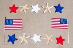 Banderas americanas con las estrellas de mar en la playa arenosa Foto de archivo