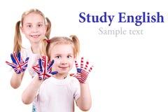 Banderas americanas e inglesas en las manos del niño. Fotografía de archivo