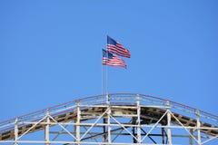 Banderas americanas sobre la montaña rusa Imágenes de archivo libres de regalías
