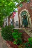 Banderas americanas y ornamentales delante de casas americanas típicas foto de archivo