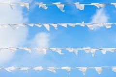 Banderas blancas de la forma triangular, banderines contra el cielo nublado azul en guirnalda horizontal Día de fiesta de la call Foto de archivo