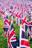 Banderas BRITÁNICAS de británicos Reino Unido en fila con el foco delantero y más lejos los símbolos borrosos con el bokeh Las ba Imagen de archivo libre de regalías