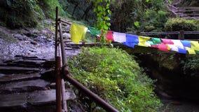 Banderas budistas del rezo que cuelgan a lo largo de caminar las trayectorias en Nepal El emigrar en el Himalaya metrajes