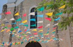 Banderas coloreadas delante de la iglesia católica mexicana Fotografía de archivo libre de regalías