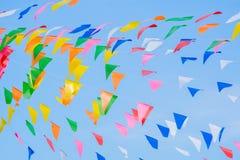 Banderas coloreadas multi del arco iris del partido en el cielo azul para la celebración Imagen de archivo libre de regalías