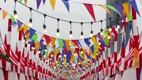 Banderas coloreadas triangulares y oscilación de la bombilla en el viento Está para la decoración en una celebración de la alegrí metrajes