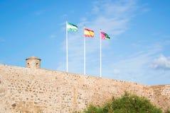 Banderas coloridas brillantes sobre la pared de piedra antigua de Gibralfaro Imagen de archivo