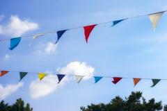 Banderas coloridas de la decoración contra el cielo azul Imagenes de archivo