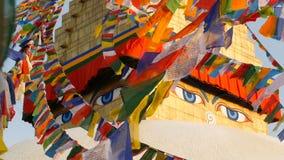Banderas coloridas del rezo que vuelan en el viento en Boudhanath Stupa, pagoda santa, símbolo de Nepal y Katmandu con golgen almacen de metraje de vídeo
