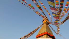 Banderas coloridas del rezo que vuelan en el viento en Boudhanath Stupa, pagoda santa, símbolo de Nepal y Katmandu con golgen almacen de video