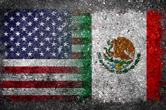 Banderas combinadas de los E.E.U.U. y de México pintados en el muro de cemento Fotografía de archivo