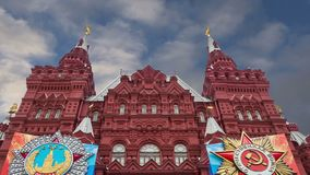 Banderas con las medallas y cintas en la fachada de la decoración histórica de Victory Day del museo, Plaza Roja, Moscú, Rusia almacen de metraje de vídeo