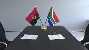 Banderas de Angola y de Suráfrica y papeles en la tabla Negociaciones y firma de un acuerdo internacional almacen de metraje de vídeo