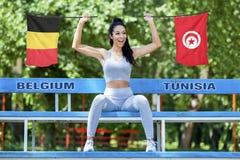 Banderas de Bélgica y de Túnez que son sostenidos por la muchacha atractiva hermosa fotos de archivo