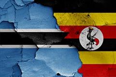 Banderas de Botswana y de Uganda pintados en la pared Foto de archivo libre de regalías