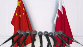 Banderas de China y de Bahrein en la rueda de prensa internacional de la reunión o de las negociaciones animación 3D metrajes