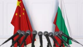 Banderas de China y de Bulgaria en la rueda de prensa internacional de la reunión o de las negociaciones animación 3D metrajes