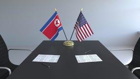Banderas de Corea del Norte y de los Estados Unidos y papeles en la tabla Negociaciones y firma de un acuerdo internacional almacen de metraje de vídeo