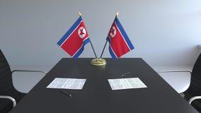 Banderas de Corea del Norte y de papeles en la tabla Negociaciones y firma de un acuerdo Animación conceptual 3D almacen de video