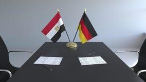 Banderas de Egipto y de Alemania y papeles en la tabla Negociaciones y firma de un acuerdo internacional 3D conceptual almacen de video