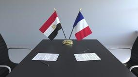 Banderas de Egipto y de Francia y papeles en la tabla Negociaciones y firma de un acuerdo internacional 3D conceptual almacen de metraje de vídeo
