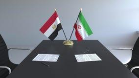 Banderas de Egipto y de Irán y papeles en la tabla Negociaciones y firma de un acuerdo internacional 3D conceptual almacen de metraje de vídeo