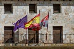 Banderas de España, Castile y León y colgante en el ¡n de Gumiel de Izà Burgos imagen de archivo