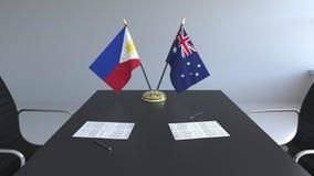 Banderas de Filipinas y de Australia y papeles en la tabla Negociaciones y firma de un acuerdo internacional metrajes