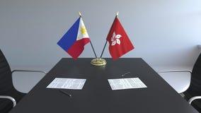 Banderas de Filipinas y Hong Kong y papeles en la tabla Negociaciones y firma de un acuerdo internacional almacen de video