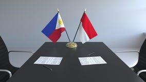 Banderas de Filipinas y de Indonesia y papeles en la tabla Negociaciones y firma de un acuerdo internacional almacen de metraje de vídeo