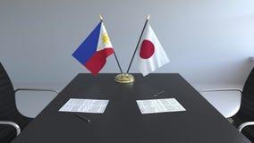 Banderas de Filipinas y de Japón y papeles en la tabla Negociaciones y firma de un acuerdo internacional Conceptual metrajes