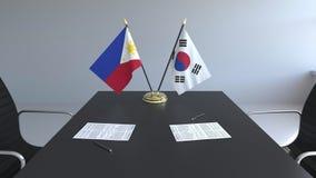 Banderas de Filipinas y de la Corea del Sur y papeles en la tabla Negociaciones y firma de un acuerdo internacional almacen de metraje de vídeo
