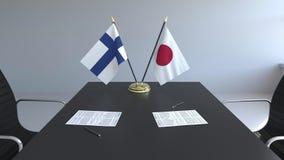 Banderas de Finlandia y de Japón y papeles en la tabla Negociaciones y firma de un acuerdo internacional 3D conceptual metrajes