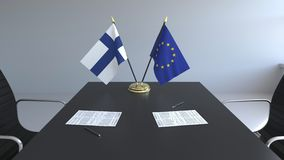 Banderas de Finlandia y la unión europea y los papeles en la tabla Negociaciones y firma de un acuerdo internacional metrajes