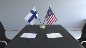 Banderas de Finlandia y de los Estados Unidos y papeles en la tabla Negociaciones y firma de un acuerdo internacional almacen de metraje de vídeo
