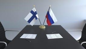 Banderas de Finlandia y de Rusia y papeles en la tabla Negociaciones y firma de un acuerdo internacional 3D conceptual almacen de metraje de vídeo