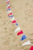Banderas de golpe ligero coloreadas en superficie de la arena Imágenes de archivo libres de regalías