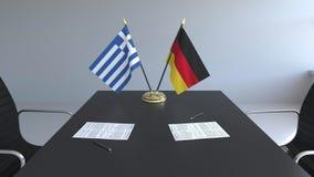 Banderas de Grecia y de Alemania y papeles en la tabla Negociaciones y firma de un acuerdo internacional 3D conceptual metrajes