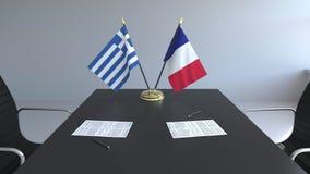 Banderas de Grecia y de Francia y papeles en la tabla Negociaciones y firma de un acuerdo internacional 3D conceptual almacen de metraje de vídeo