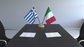 Banderas de Grecia y de Italia y papeles en la tabla Negociaciones y firma de un acuerdo internacional 3D conceptual almacen de video