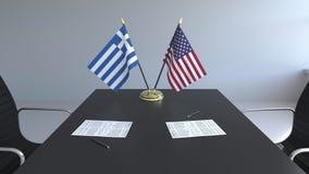 Banderas de Grecia y de los E.E.U.U. y papeles en la tabla Negociaciones y firma de un acuerdo internacional 3D conceptual metrajes