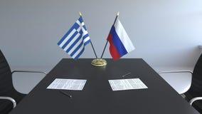Banderas de Grecia y de Rusia y papeles en la tabla Negociaciones y firma de un acuerdo internacional 3D conceptual metrajes