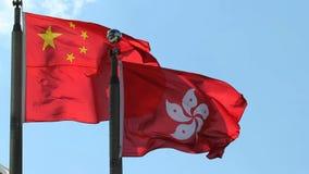 Banderas de Hong Kong y de República Popular China que vuelan de lado a lado contra el cielo azul claro en un día ventoso 1080p almacen de metraje de vídeo